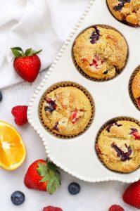 Gluten Free Orange Triple Berry Muffins in a White Ceramic Muffin Pan