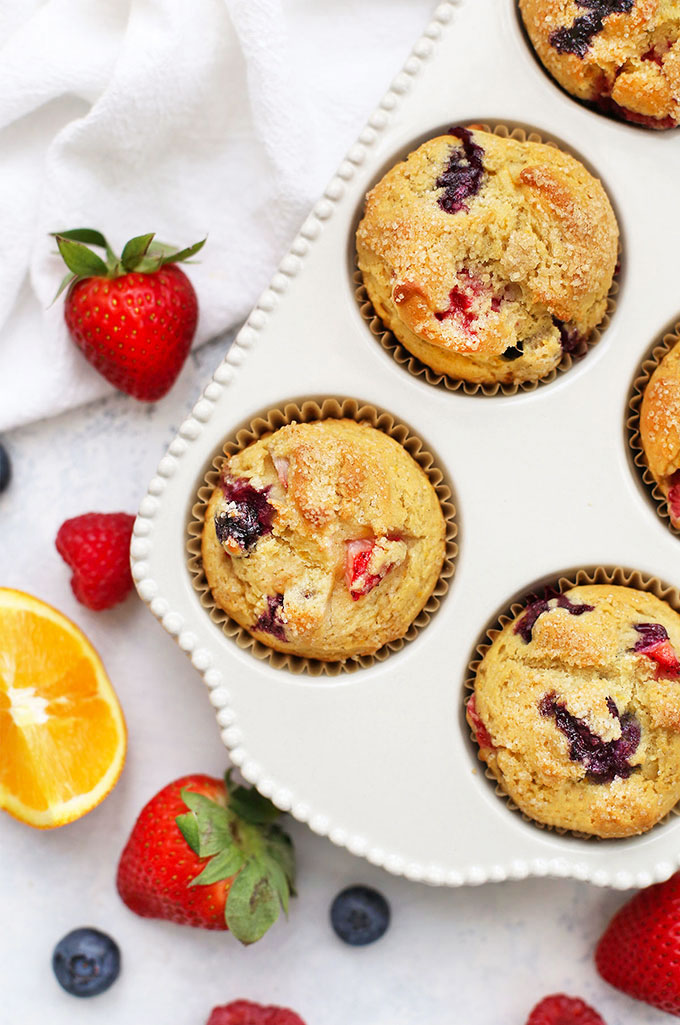 Gluten Free Orange Triple Berry Muffins in a White Ceramic Muffin Pan