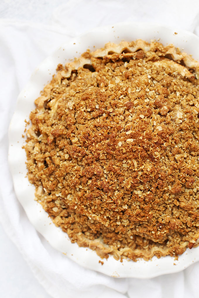 Overhead view of a gluten free apple crumble pie in a white pie pan.