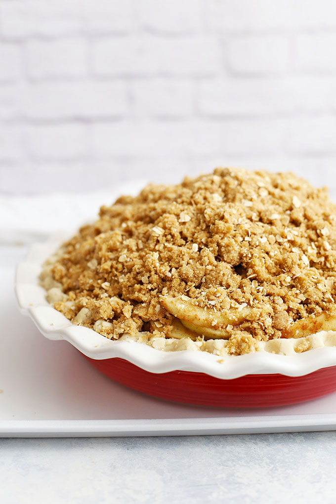 Front view of an unbaked apple crumble pie ready to go into the oven.