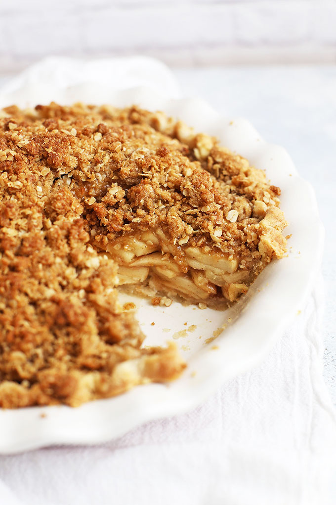 Front view of an apple crumble pie with a slice out of it.