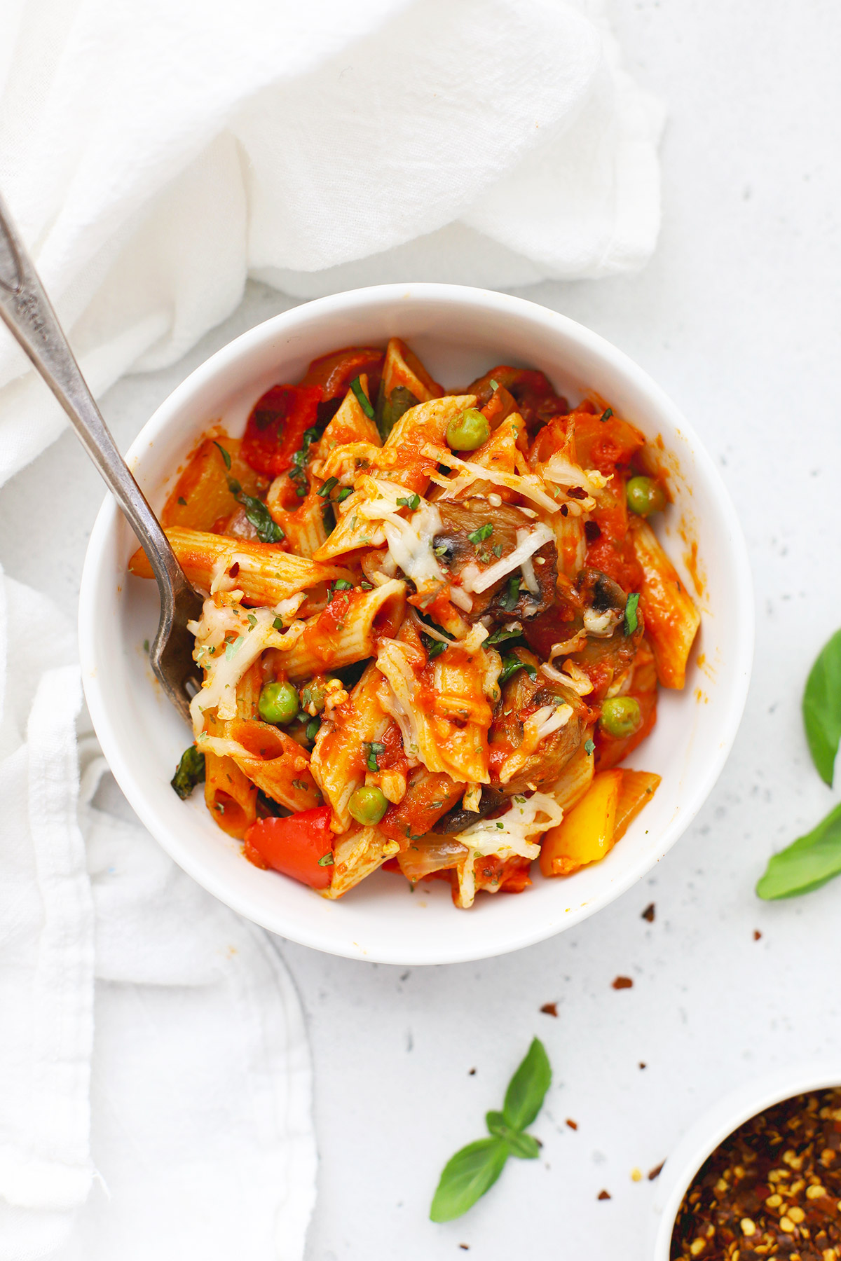 A white bowl of baked penne with roasted veggies