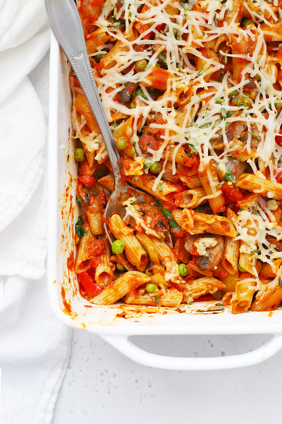 Overhead view of a spoon scooping out a serving of gluten free baked penne with roasted veggies