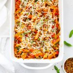 White baking dish full of baked penne with roasted veggies