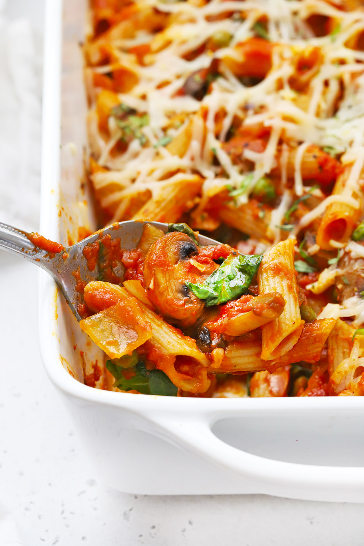 Close up view of a spoon scooping out a serving of baked penne with roasted veggies from the pan