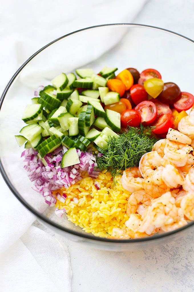 Ingredients for gluten free lemon dill shrimp orzo salad in a bowl - gluten free orzo, cooked shrimp, cherry tomatoes, cucumber, dill, and red onion