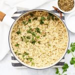 Overhead view of cooked quinoa in a saucepan with fresh herbs, salt and pepper