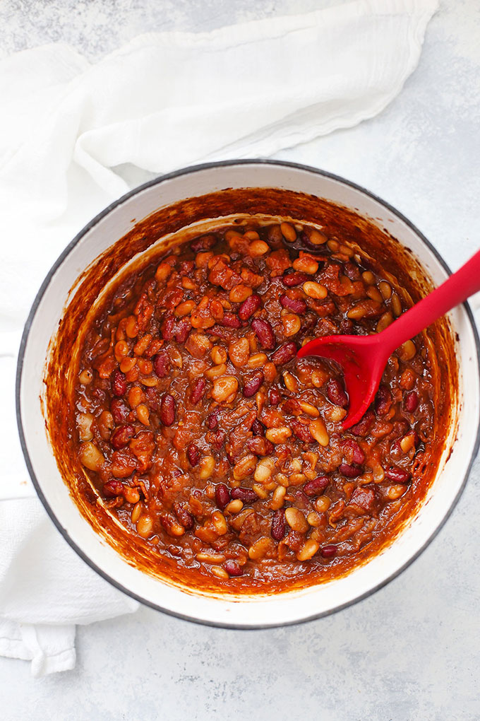 Overhead view of Settlers Baked Beans in a white cast iron pan, being stirred with a red spoon.