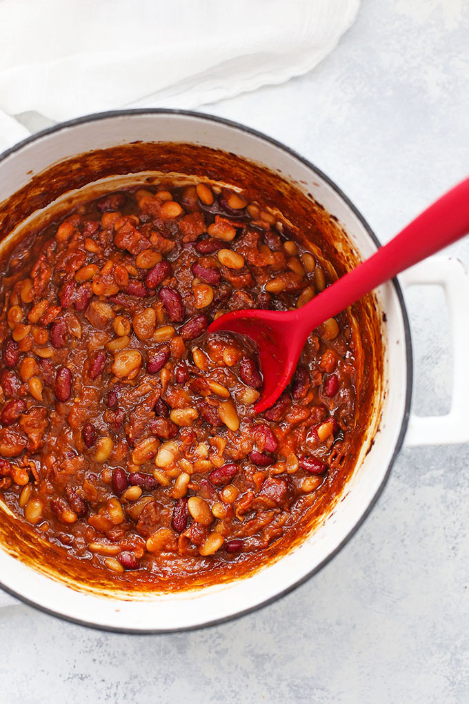 Spoon stirring pot of Settlers Baked Beans from One Lovely Life