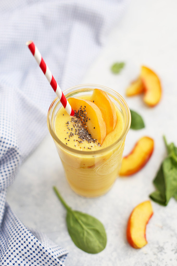 Peach Mango Smoothie in a glass topped with fresh peach slices and chia seeds