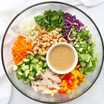 Thai Chopped Salad from One Lovely Life, with lettuce, cabbage, carrots, pepper, cucumber, green onions, cilantro, chicken, and Thai peanut sauce drizzle