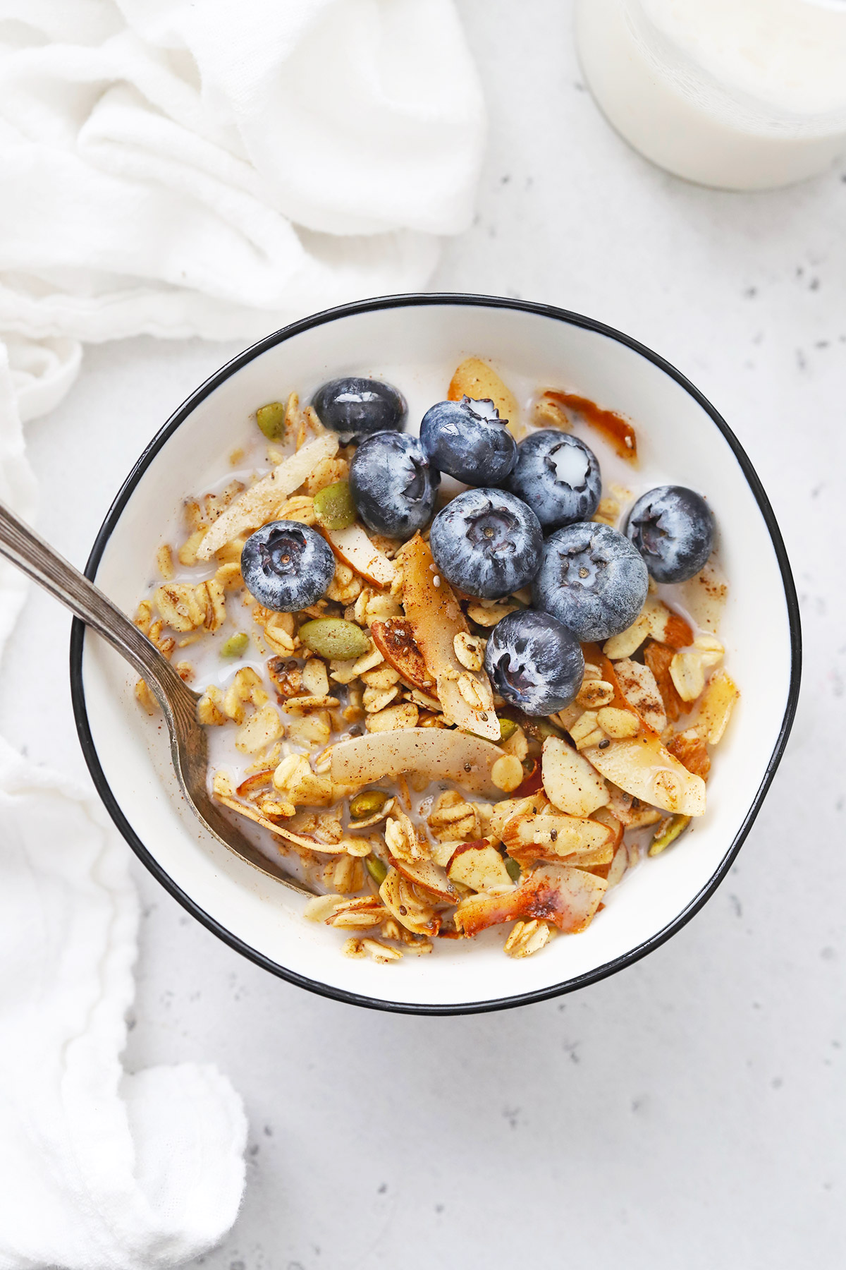 Bowl of Gluten Free Warm Spiced Granola with almond milk and blueberries