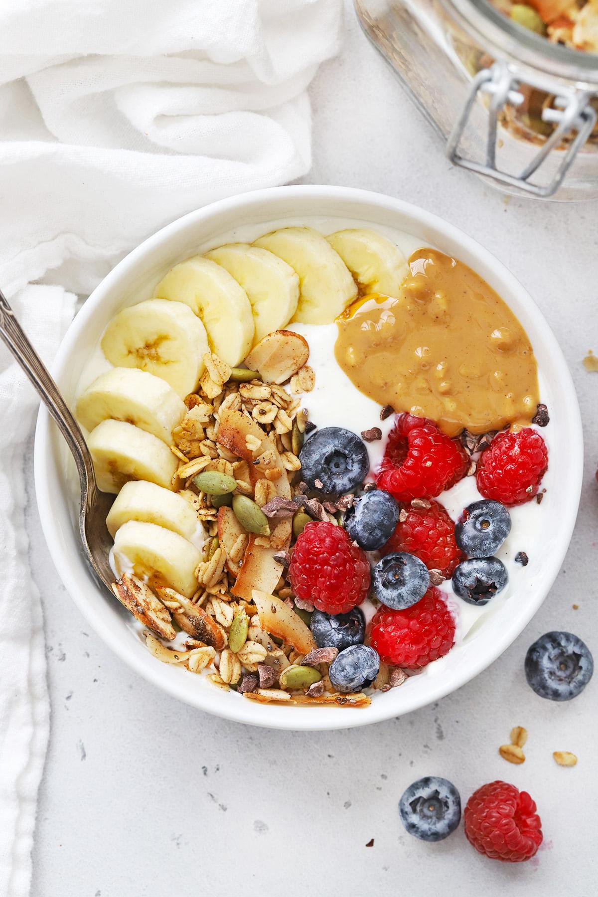Yogurt Bowl with Warm Spiced Granola, fresh berries, sliced banana, and peanut butter