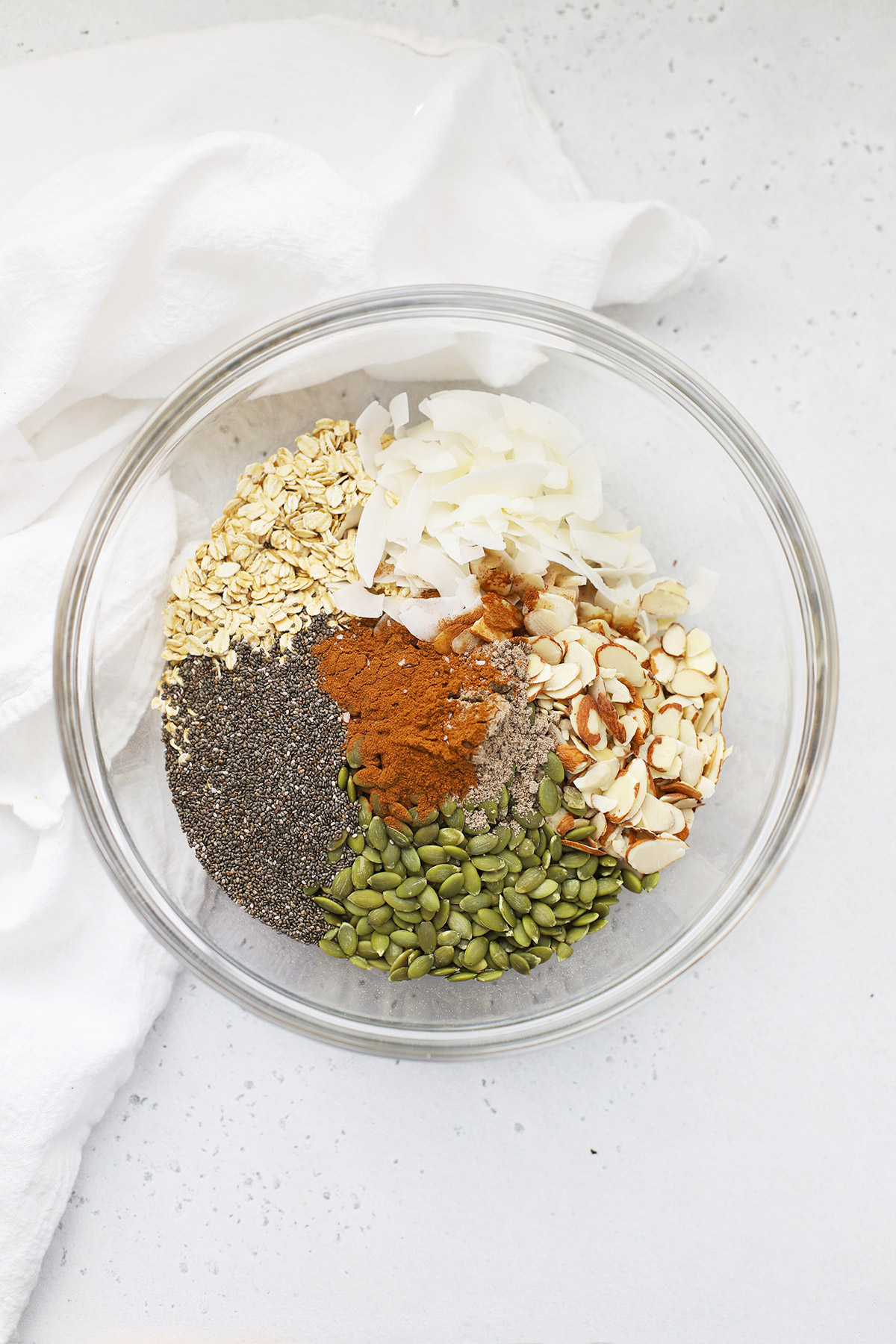 Large glass mixing bowl of ingredients for warm spiced granola