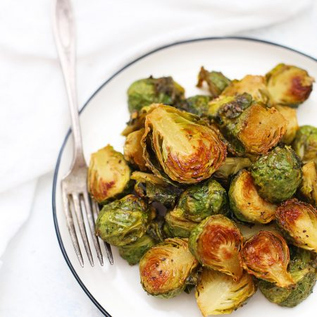 Close up overhead view of a plate of roasted maple dijon Brussels sprouts.