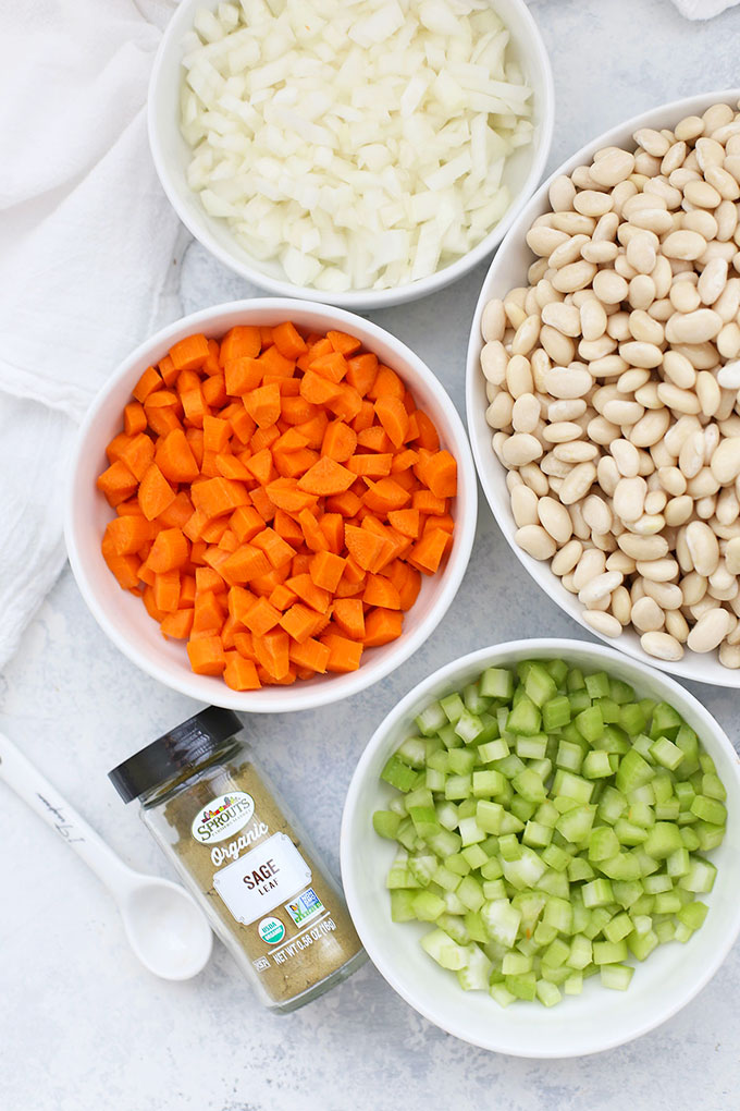 Ingredients for Slow Cooker Vegetable Bean Soup - Bowl of Great Northern beans, bowl of onions, bowl of diced carrots, bowl of diced celery, Sprouts brand organic sage, and a teaspoon.