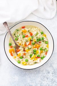 A Bowl of Gluten Free Dairy Free Chicken Vegetable Risotto with a spoon dipped in.