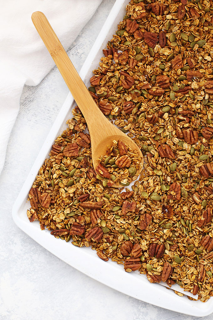 White sheet pan full of maple pumpkin pecan granola with a spoon scooping.