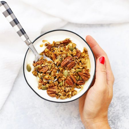Hand holding a bowl of Maple Pumpkin Pecan Granola with Yogurt and a Black and White Gingham Spoon