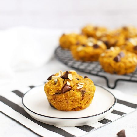 Close up view of Gluten Free Pumpkin Chocolate Chip Muffin on a plate with a striped napkin.