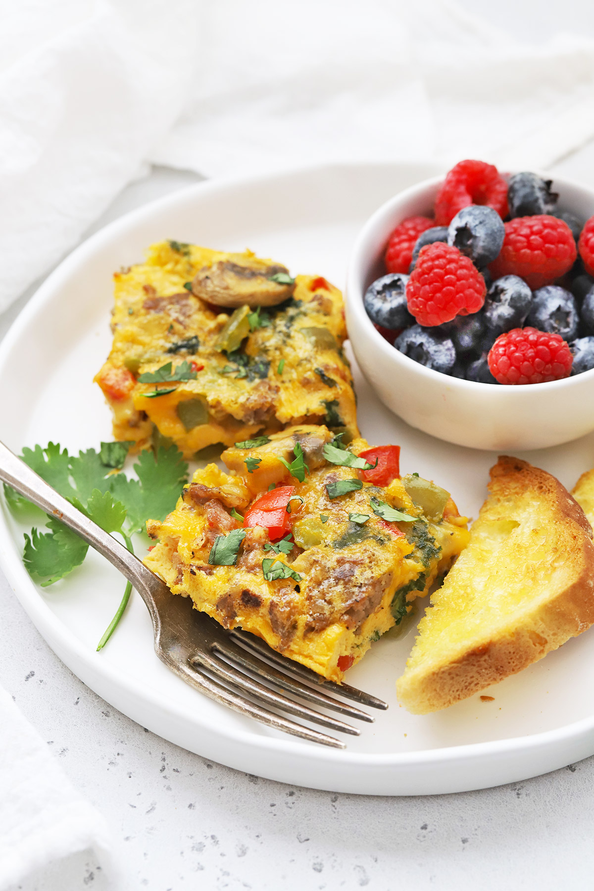 Two slices of sausage and veggie breakfast casserole on a plate with fresh berries and gluten free toast