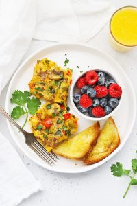 Overhead view of two slices of sausage and veggie breakfast bake, gluten free toast + fresh berries