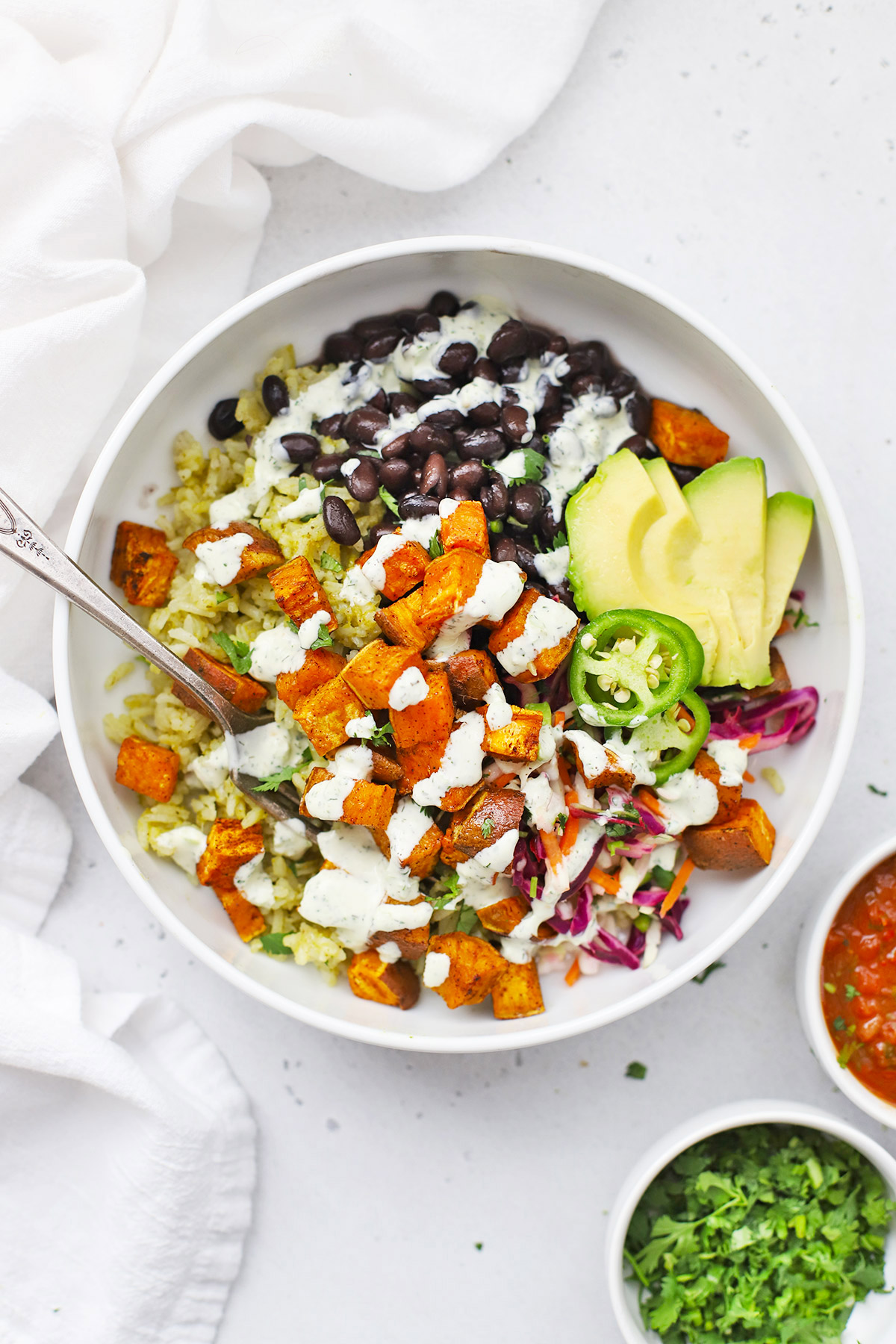 Overhead view of a Chipotle Sweet Potato Burrito Bowl with beans, rice, veggies, and tomatillo ranch dressing.