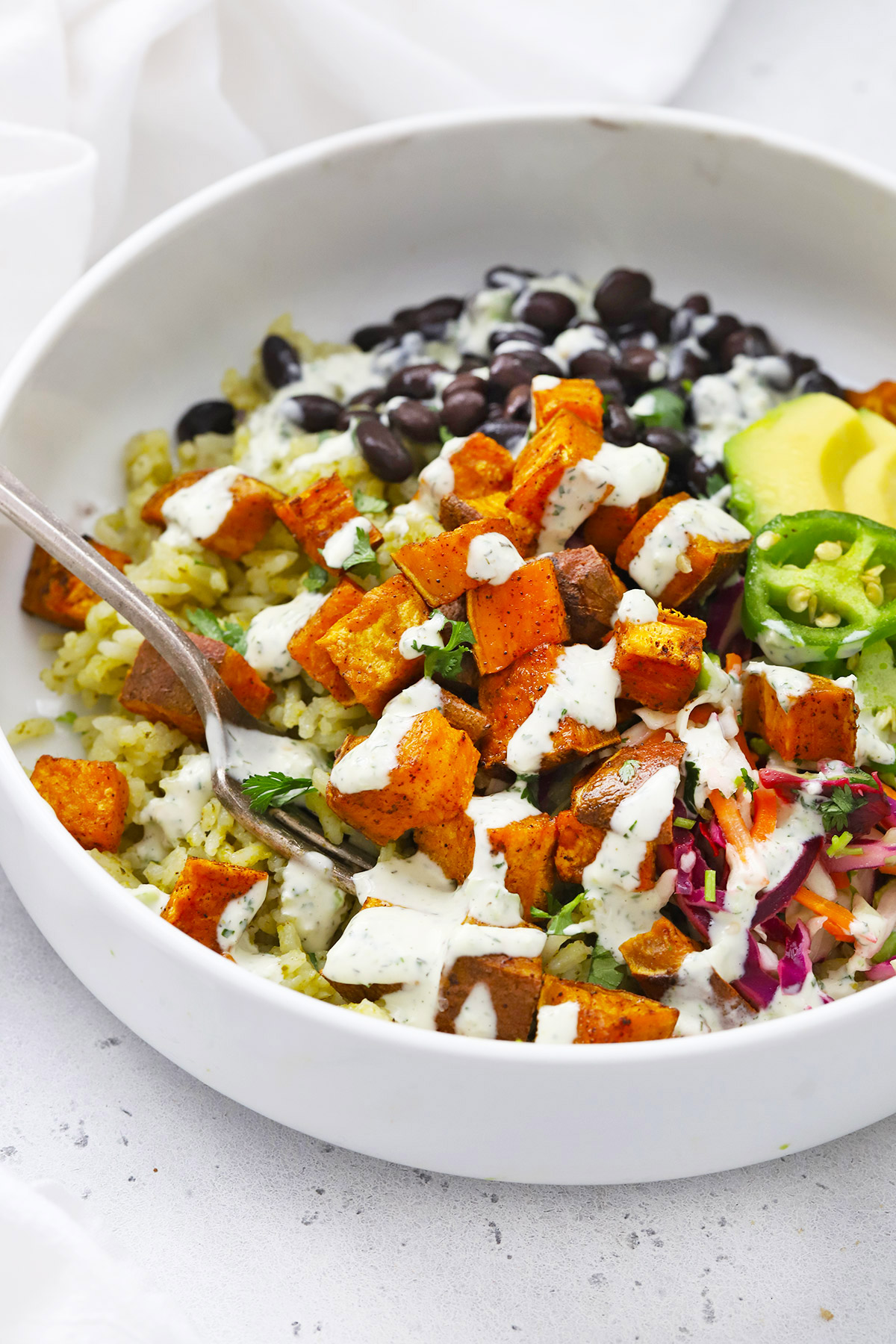 Close up view of Chipotle Sweet Potato Burrito Bowl drizzled with tomatillo ranch dressing