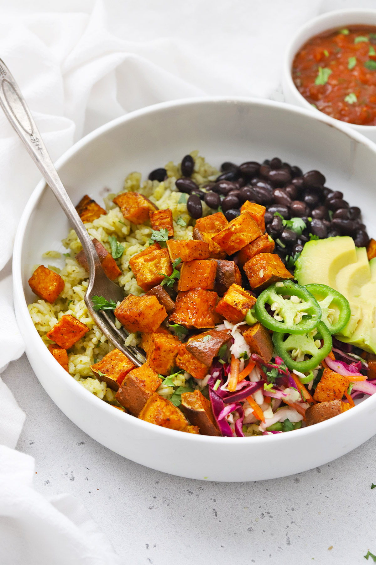 White bowl with chipotle sweet potatoes, black beans, green rice, slaw, and avocado.