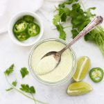 Tomatillo Ranch Dressing in a jar with a spoon. Jalapeño, lime, and cilantro garnish.