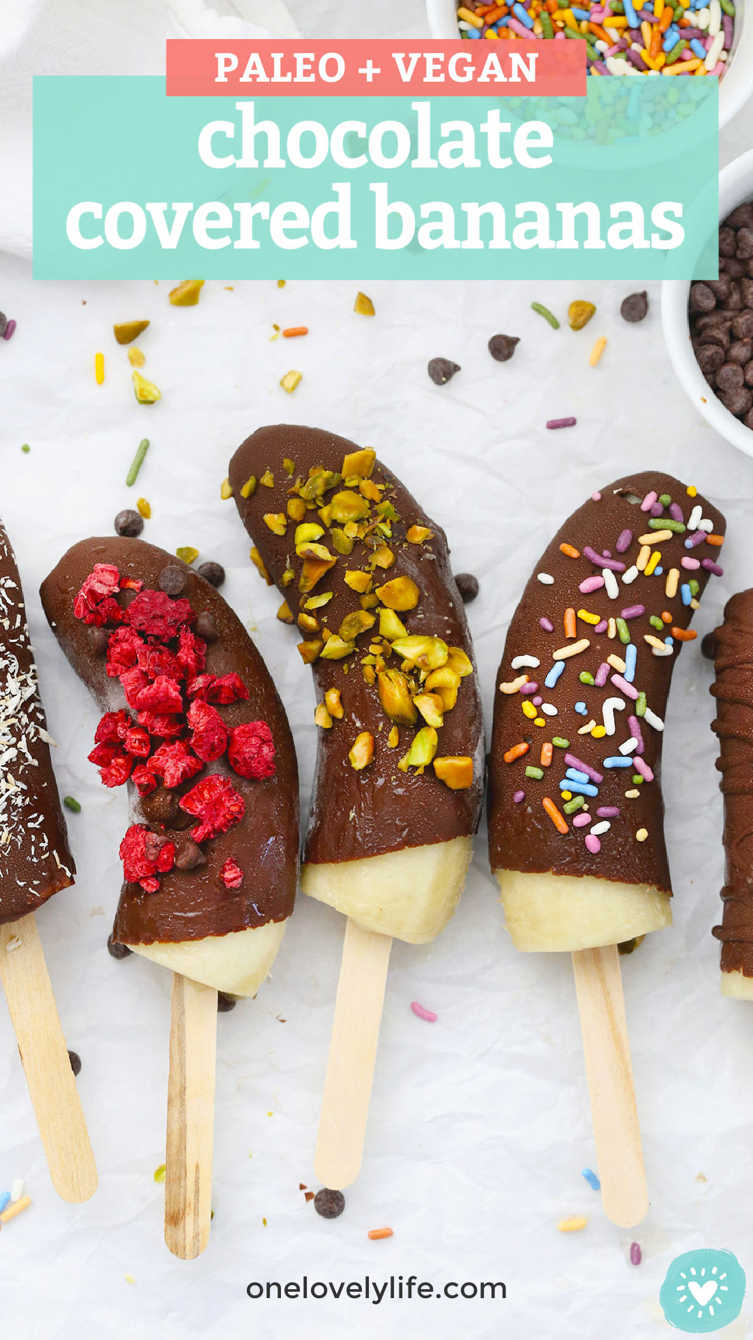 Frozen Chocolate Covered Bananas with different toppings on a piece of parchment paper