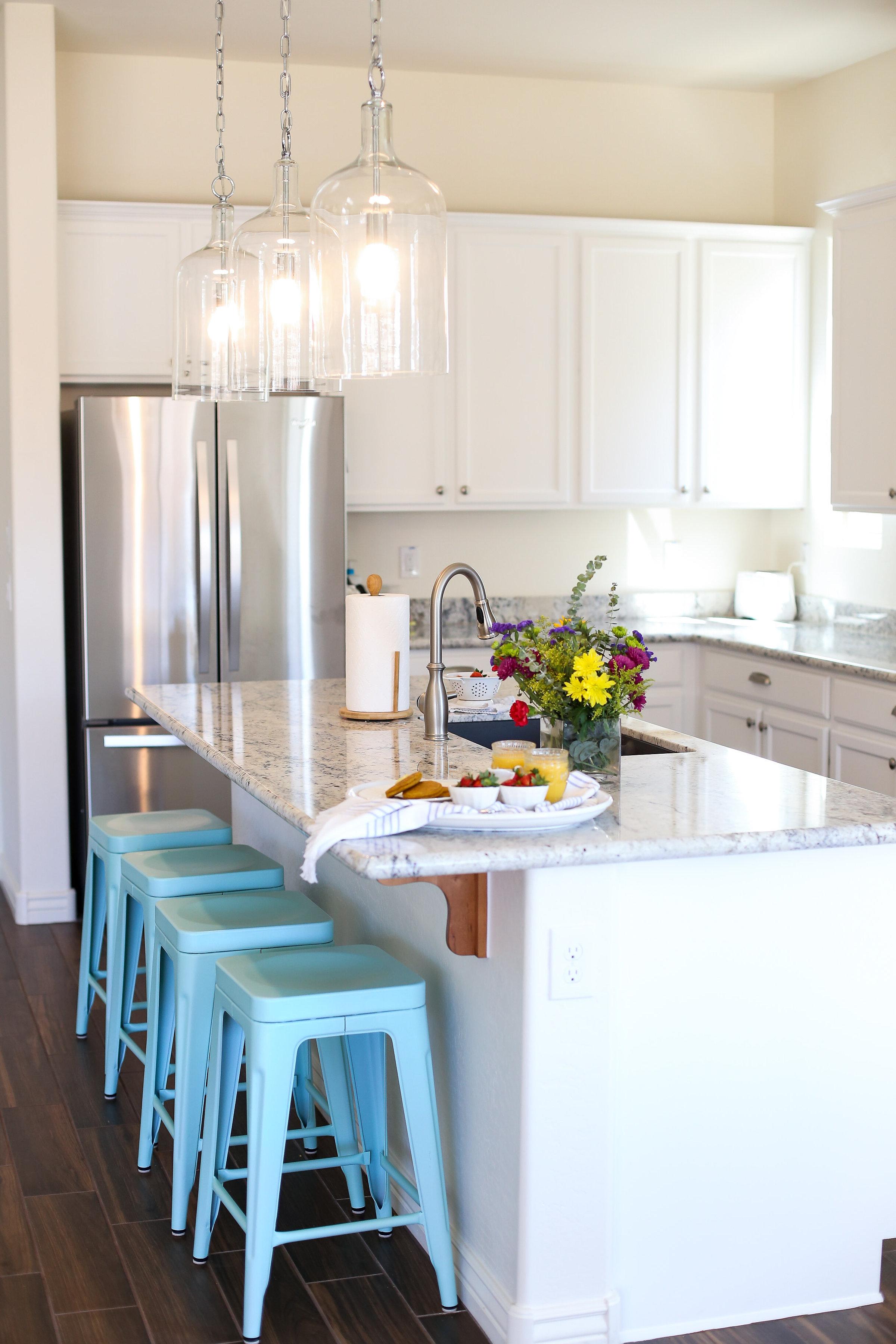 Capri pendants, aqua metal stools, wood tile, and white ice granite. I love this kitchen!