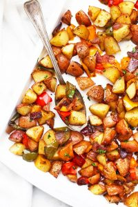 Sheet pan of roasted breakfast potatoes and veggies with a spoon taking a scoop