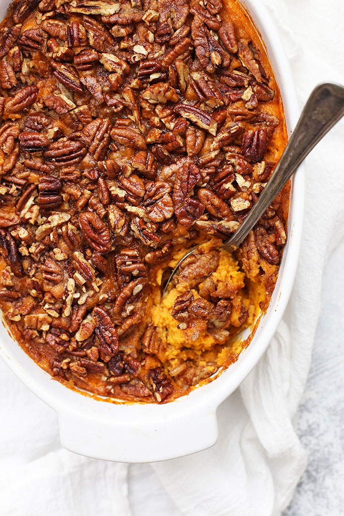 Overhead view of Paleo Sweet Potato Casserole with Pecan Topping. Spoon scooping out a serving.