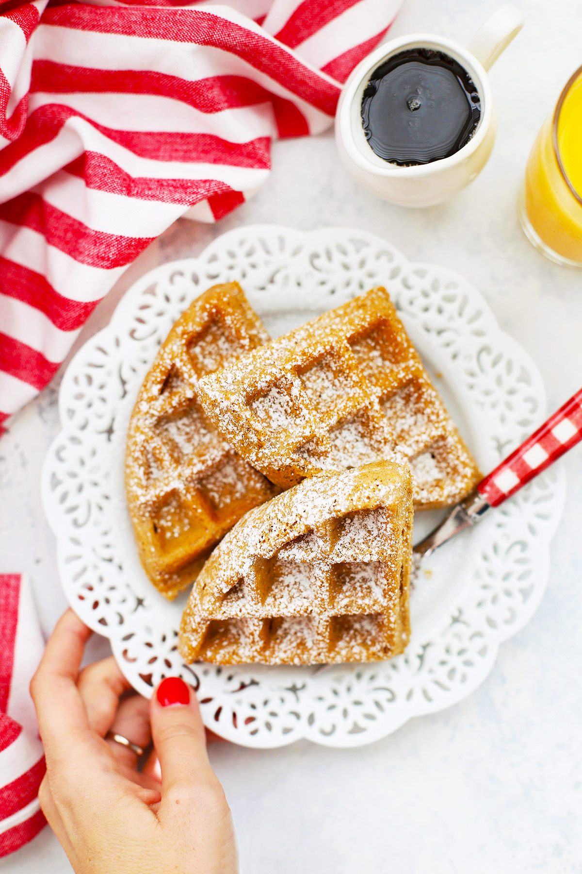 Overhead view of 3 gluten-free gingerbread waffles topped with powdered sugar on a white lace plate
