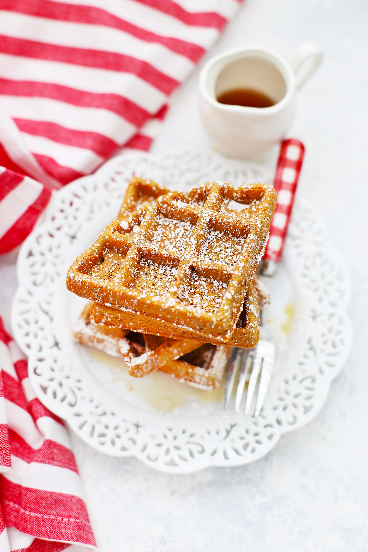 Front view of a stack of gluten-free gingerbread waffles on a white lace plate topped with powdered sugar