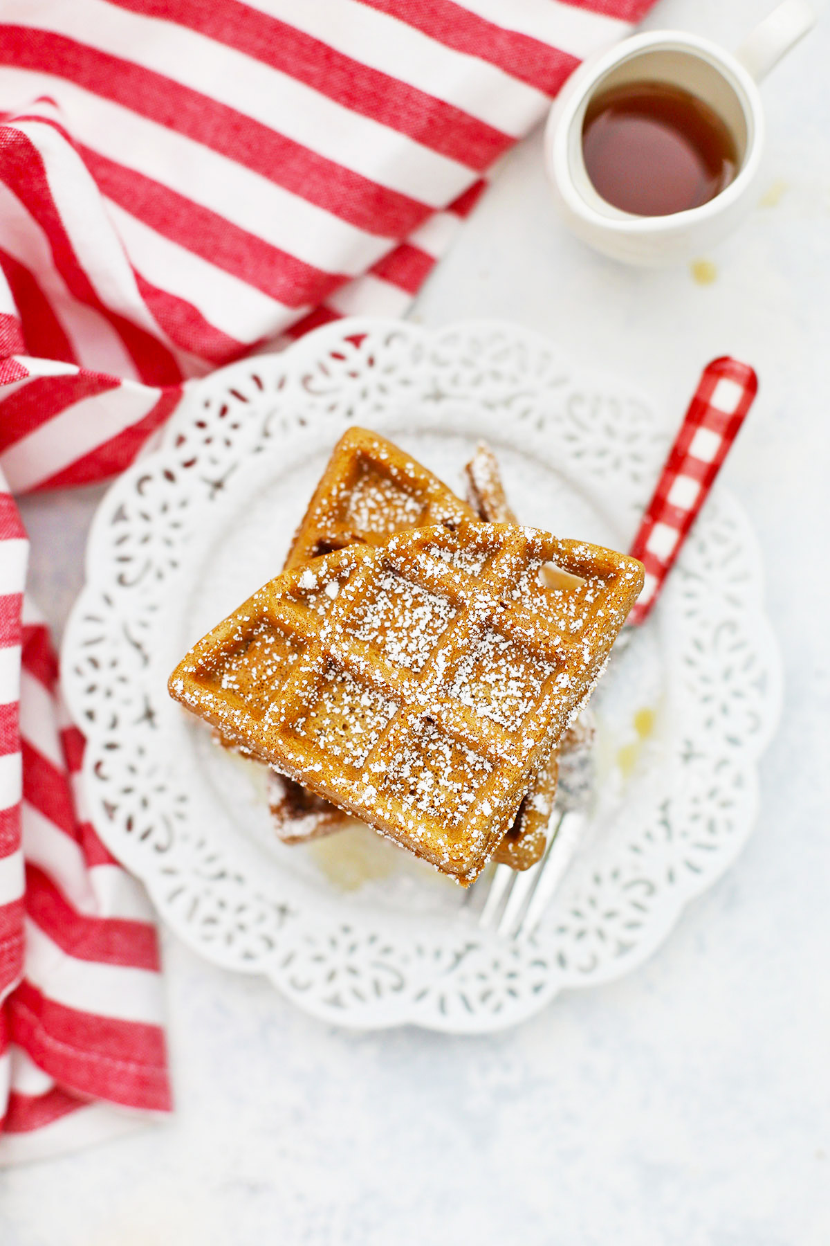 Overhead view of a stack of gluten-free gingerbread waffles topped with powdered sugar on a white lace plate