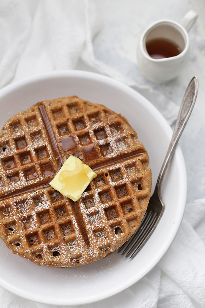 Overhead photo of a stack of gluten free gingerbread waffles with butter and maple syrup.