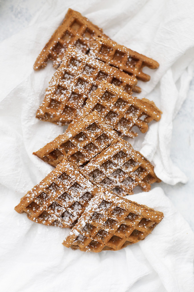 Overhead view of gingerbread waffles sprinkled with powdered sugar