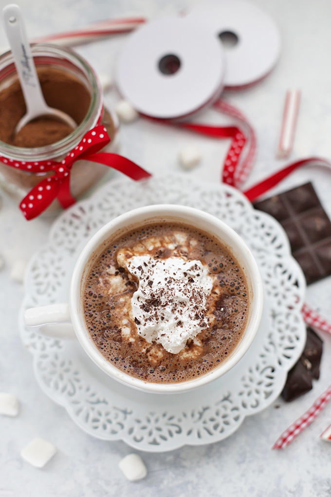 Overhead view of vegan hot chocolate topped with coconut whipped cream and shaved chocolate.