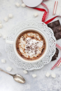 Overhead view of vegan hot chocolate in a white mug with coconut whipped cream and grated chocolate.