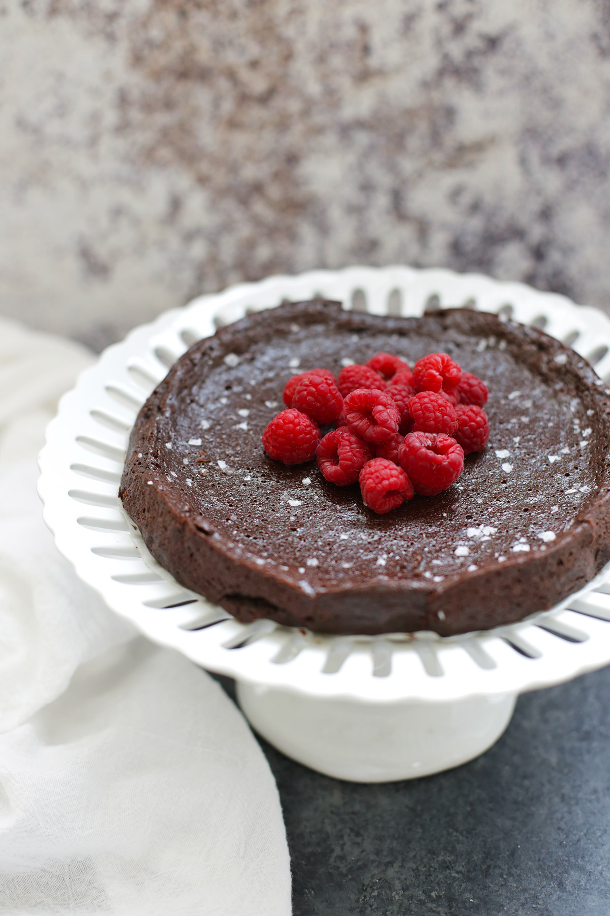 Front view of a flourless chocolate cake topped with raspberries on a white cake stand
