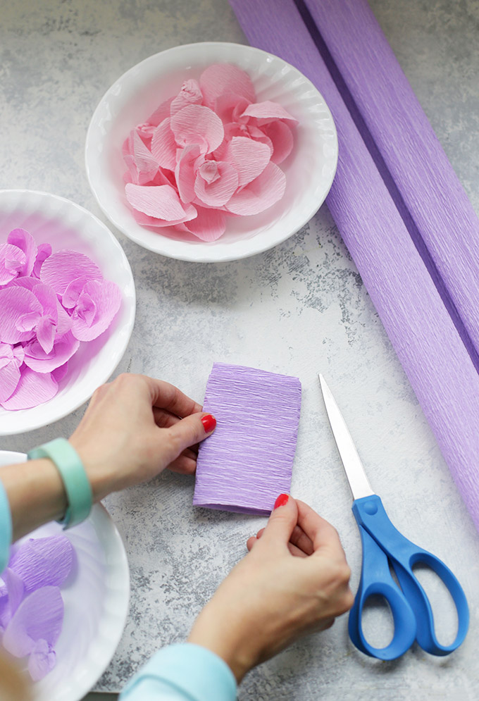 Folding purple crepe paper to make paper wisteria