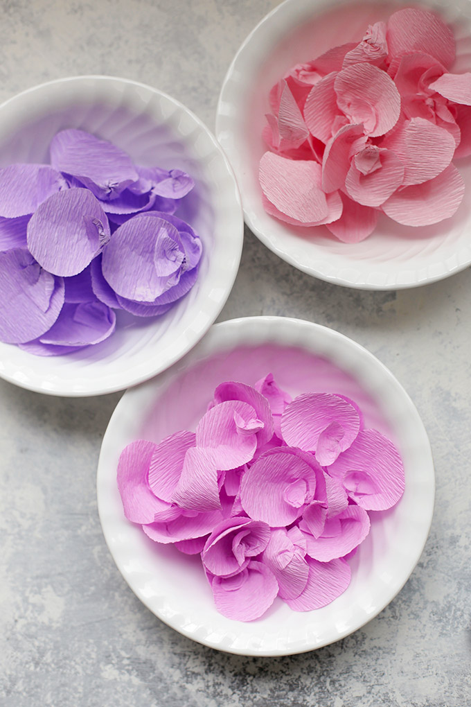 Bowls of paper wisteria petals ready to string on thread.