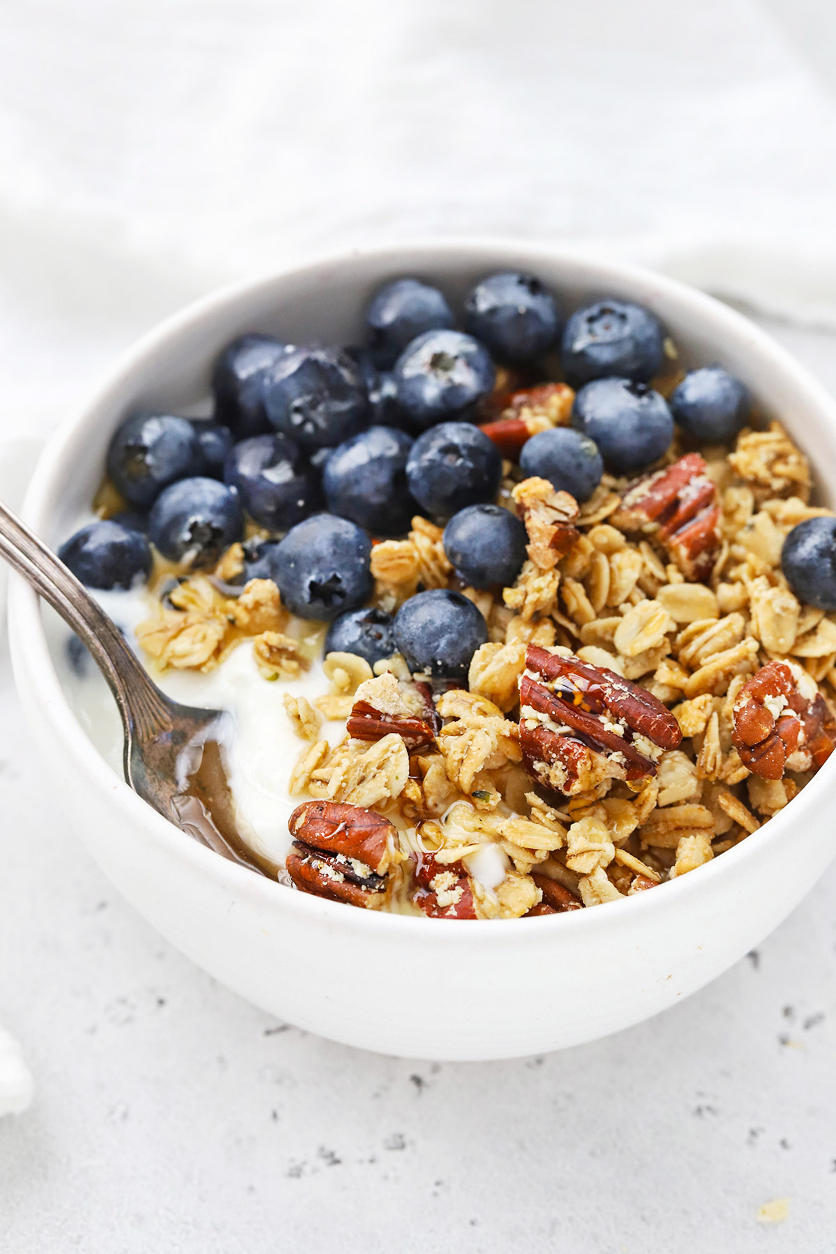 Front view of a bowl of yogurt topped with homemade maple pecan granola and fresh blueberries