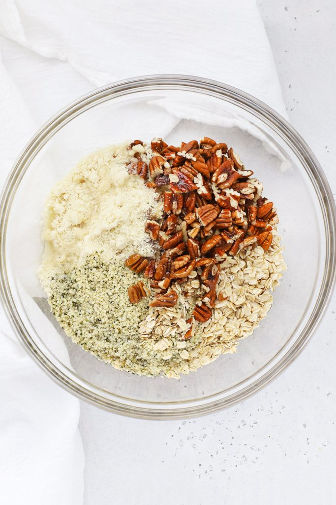 Overhead view of a bowl with ingredients for maple pecan granola