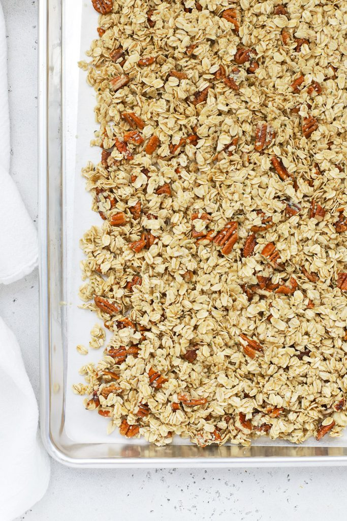Overhead view of a sheet pan with maple pecan granola ready to go into the oven