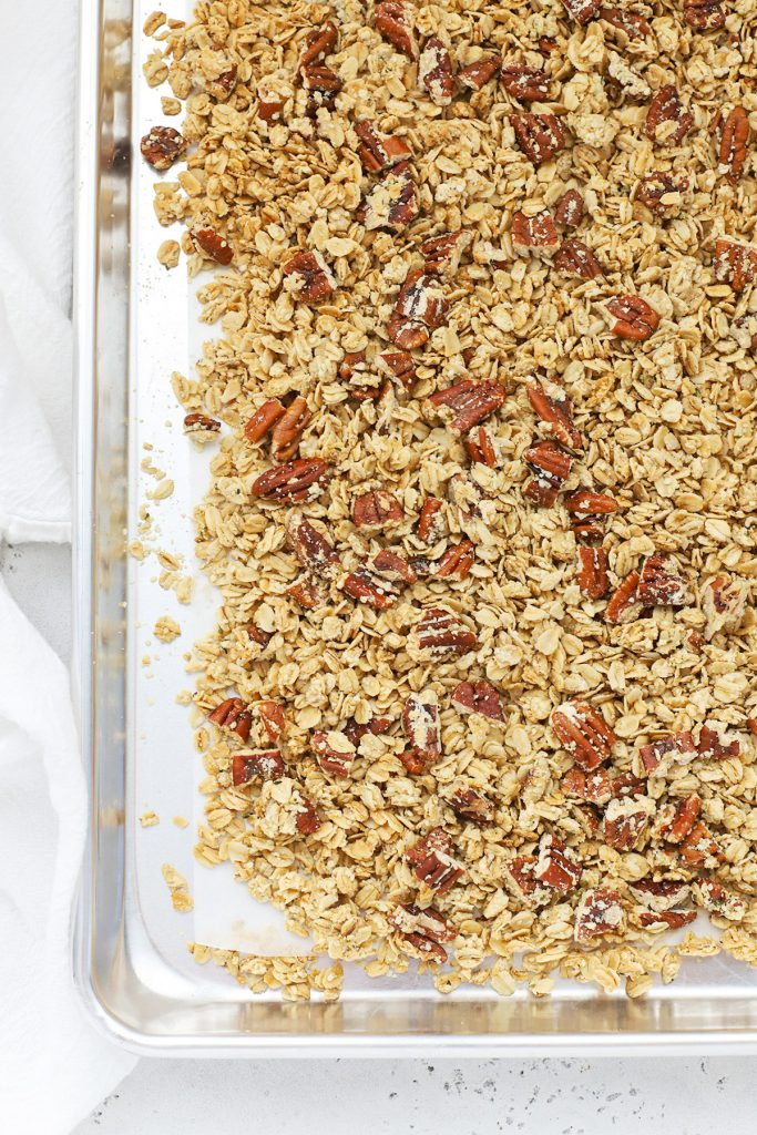 Overhead view of a sheet pan with maple pecan granola fresh from the oven