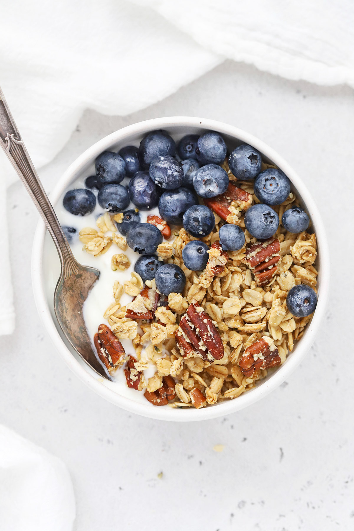 Overhead view of a bowl of yogurt topped with homemade maple pecan granola and fresh blueberries