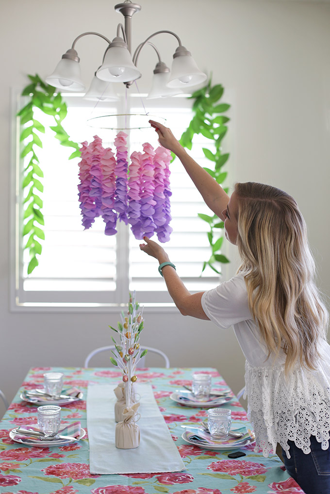 Emily Dixon from One Lovely Life hanging paper wisteria in her dining room